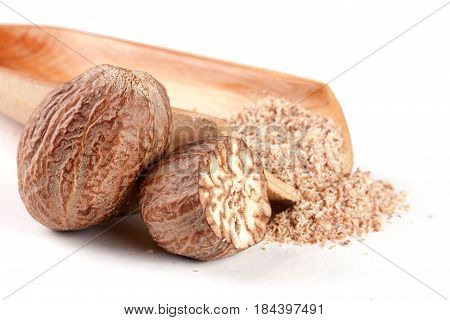nutmeg and half with powder in a scoop isolated on white background.
