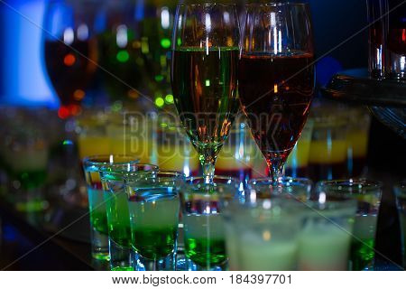 set of cocktails soft and long drinks on blurred background glasses with alcoholic layered shots mixed multicolored drink served in rows on countertop in bar or night club on blurred background