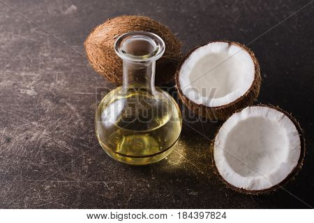 Coconut and coconut oil on a dark marble background. Exotic large walnut. Personal care. Spa treatments. Yellow oil. Fresh oil. Oil for massage. Oil for treatment