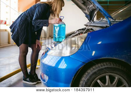 Woman Near Car's Hood. Young Blonde In Covered Parking Of Shopping Center, Stands Near Car With Rais