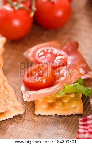 Crackers with ham and tomato on cutting board.