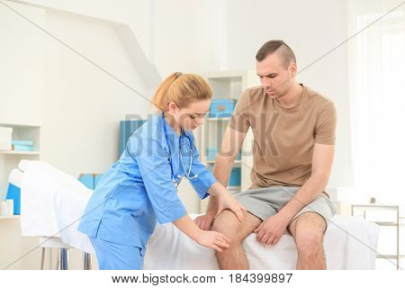 Female orthopedist examining patient in her office