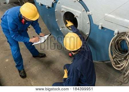 Asian expert checking the quality requirements of manufactured industrial steam boilers poster