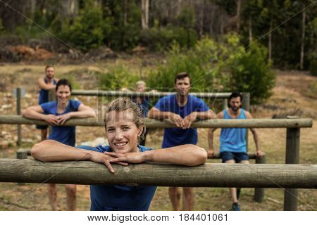 Group of people leaning on hurdles during obstacle training in boot camp