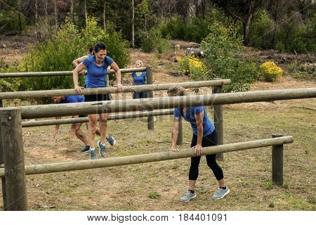 People jumping over the hurdles during obstacle course in boot camp