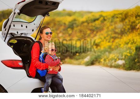 mother and little daughter travel by car in nature
