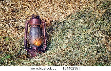 Vintage lit kerosene oil lantern lamp on straw