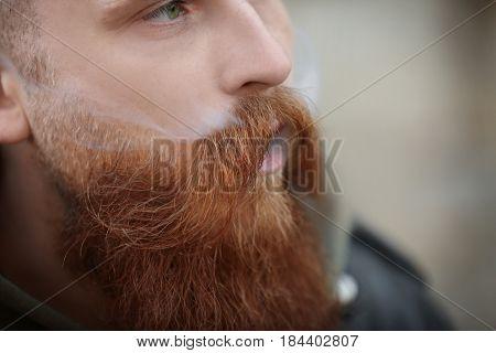 Bearded man smoking weed outdoors, closeup