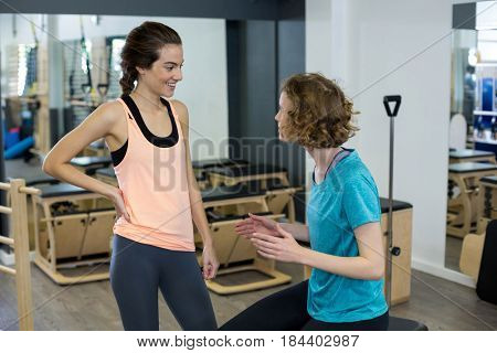 Female trainer interacting with woman in gym