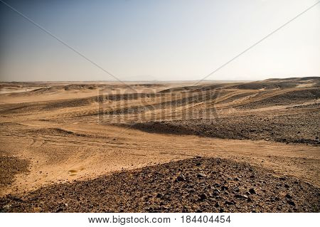 Brown sand desert dunes and hills on blue sky background. Rough roads with vehicle tracks on dry sandy land surface on sunny day. Travel destination and vacation