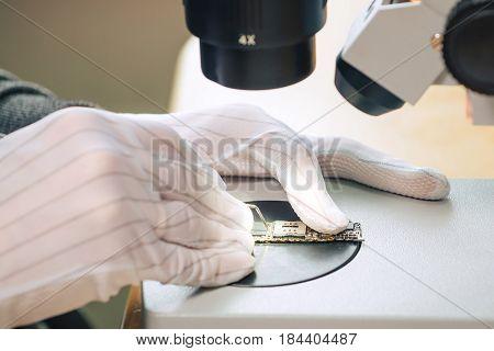 Hands of professional tech repairing small computer components on microscope table. Closeup. Electronics repair and fix service concept