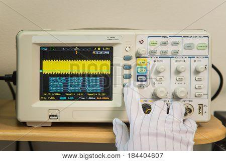 Modern oscilloscope, man's hand adjusting wave signals, closeup.