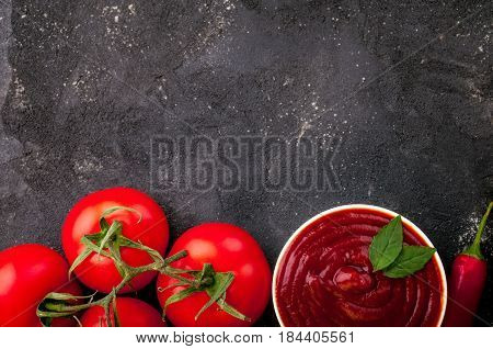 Tomato ketchup sauce in a bowl with chili basilic and tomatoes. Ingredients for cooking ketchup on dark background. Top view. Copy space