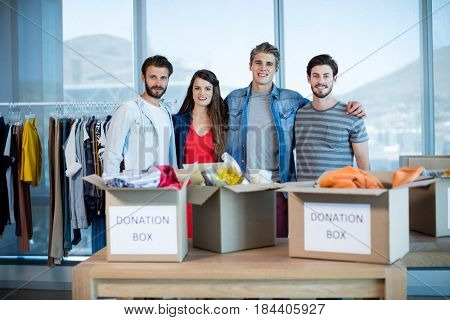 Smiling creative business team standing together with donation box in office