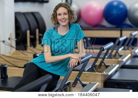 Portrait of woman relaxing on reformer in gym