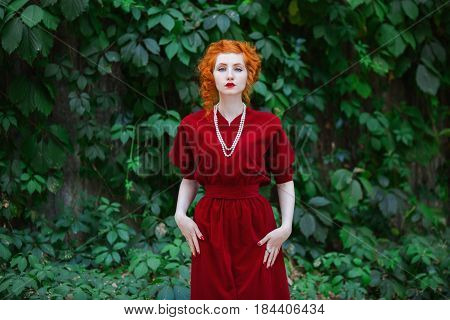 Elegance woman with red hair and red slinky dress posing on a background of green leaves. Red-haired elegance girl with pale skin and blue eyes with a bright unusual appearance with necklace of beads around her neck. Elegance model