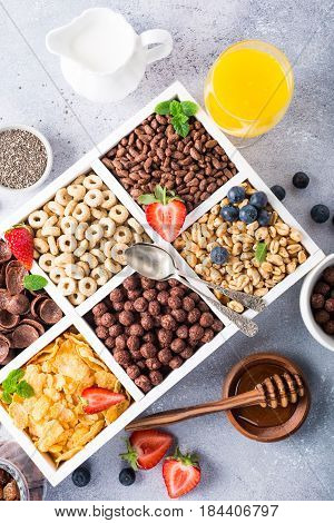 Variety of cold quick breakfast cereals with berries in white wooden box and other ingredients for breakfast, healthy eating concept, top view.