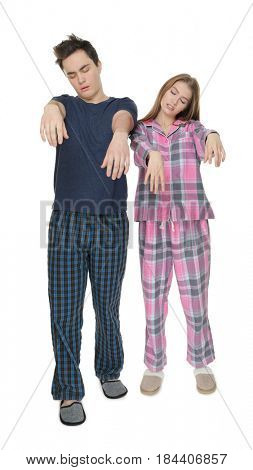 Young sleepy couple suffering from somnambulism on white background