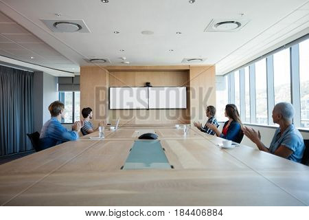 Creative business team applauding while attending a conference call in office
