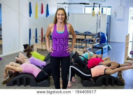 Female trainer assisting group of women with stretching exercise on arc barrel in gym