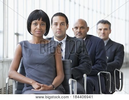 Confident business people sitting in a line