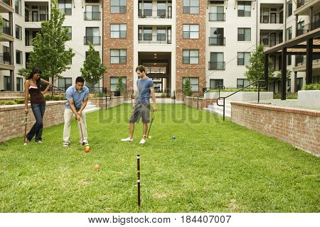 People playing croquet on lawn