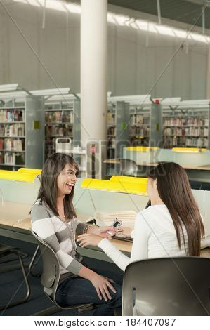 Smiling students looking at cell phone in library