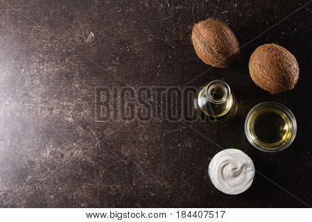 Coconut and coconut milk and oil on a dark marble background. Exotic large walnut. Personal care. Spa oil. Oil for health care. Fresh oil.Oil concept