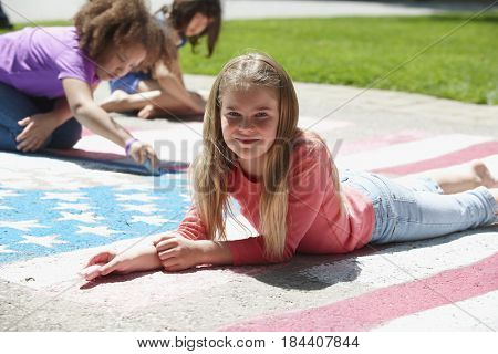Smiling girl with chalk coloring American flag on sidewalk