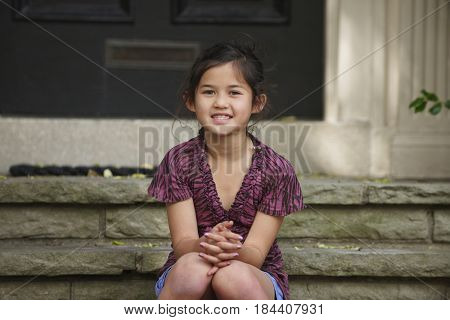 Smiling Chinese girl sitting on front stoop