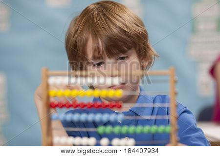 Caucasian boy using abacus in classroom