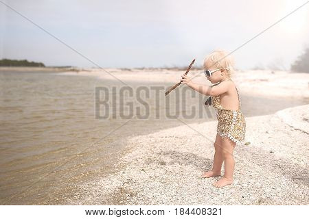 Toddler Girl Playing On Beach Throwing Sticks In The Water