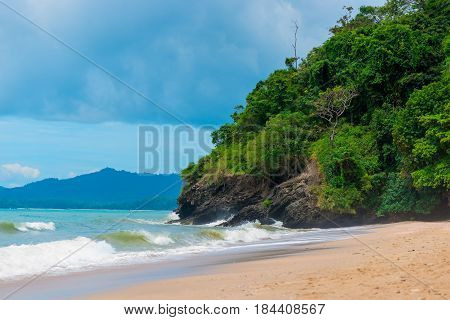 Sandy Beach And Cliffs Of Thailand In Inclement Weather, Dark Blue Sky Over The Sea