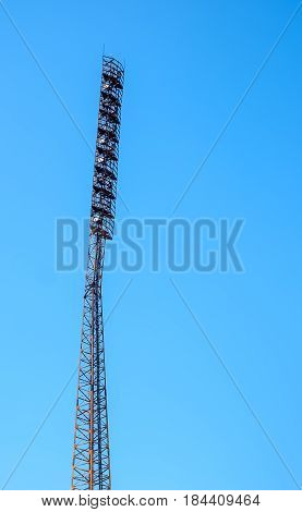 Floodlight with metal pole on blue sky
