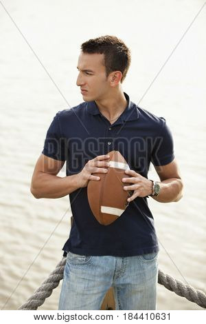Mixed race man holding football