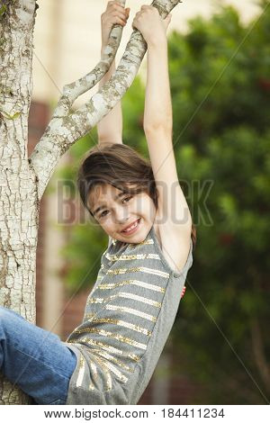Caucasian girl hanging from tree branch