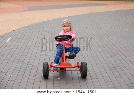 Little girl having fun driving a pedal car in spring day.