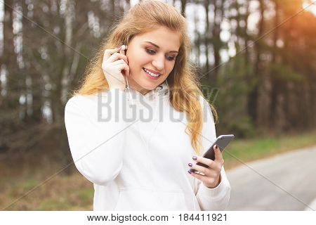 Devices For Sport. Portrait Of Young And Beautiful Redhaired Sports Girl Using Her Phone And Listeni