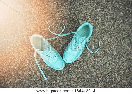 Love concept. Portrait of blue sports shoes with shoelaces shaped in form of heart on gray asphalt background.