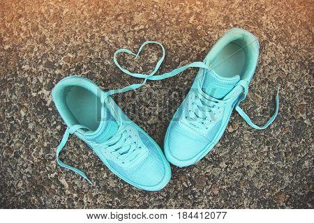 Love concept. Closeup portrait of blue sports shoes with shoelaces shaped in form of heart on gray asphalt background.