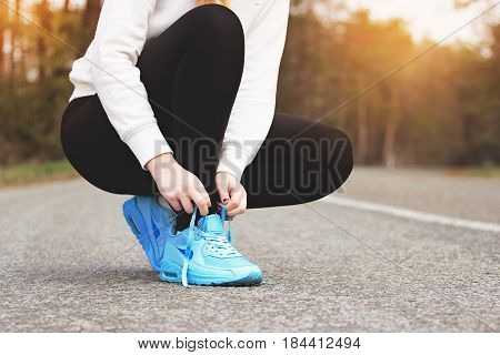 Sporty Woman. Portrait Of Young Sports Girl Tying Shoelaces On The Road. Healthy Lifestyle And Sport