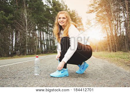 Good Sunny Running Day. Attractive And Cheerful Smiling Redhaired Sports Girl Tying Shoelaces On The