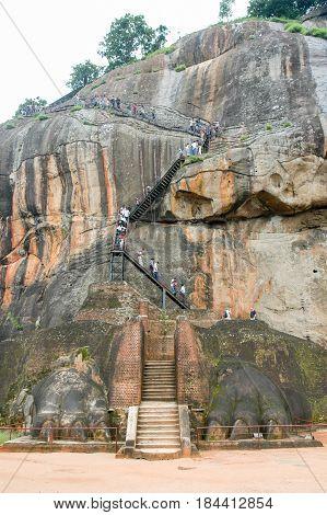 Sigiriya Sri Lanka - 18 December 2004: People climbing the stairs that lead to the rock fortress of Sigiriya on Sri Lanka