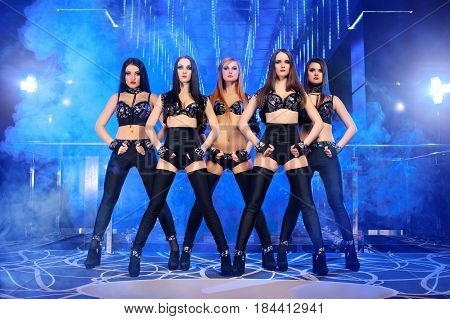 Five beautiful young females professional disco club dancers posing on stage at the nightclub performance entertainment sexy hot girls beautiful young athletic shape erotic exotic modern perform.