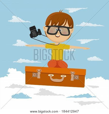 Cute little boy flying on a suitcase on background of blue sky
