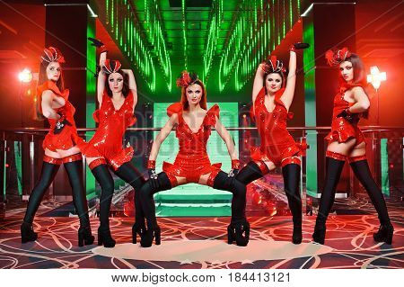 Full length portrait of a group of sexy female go-go dancers performing at the disco club wearing provocative dresses alluring tempting stage costumes erotic exotic sexuality sensual professional.