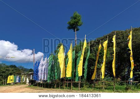 Beautiful way to Okhrey Monastery at Okhrey village colourful Buddist prayer religious flags waving on the other side of road . Okhrey is a remote village with scenic natural vista in background in Sikkim India.