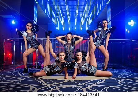 Full length portrait of five beautiful sexy go-go dancers performing together in artistic lighting at the disco club performers art festive entertaining leisure showgirls sexuality seduction feminine.