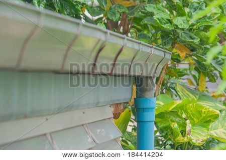 Stainless rain gutter on roof of wooden house.