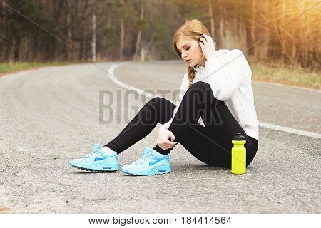 Sports Injuries. Beautiful And Young Redhaired Girl Holding Her Injured Leg And Sitting On The Park